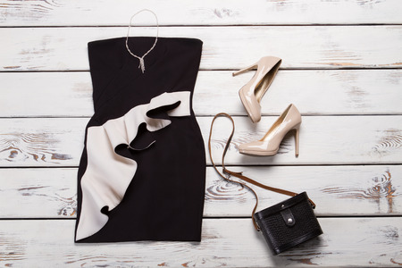 Black dress and retro purse. Dark retro bag on showcase. Ladys evening look with accessories. Outfit with jewelry and handbag.