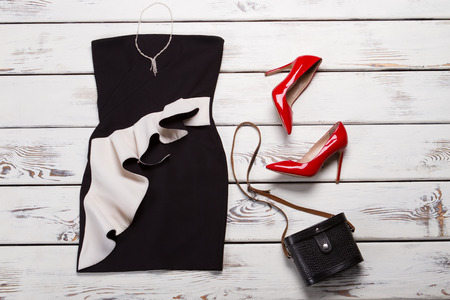 Black dress and red heels. Table with red glossy shoes. Ladys outfit with bright footwear. Luxury evening apparel on sale.