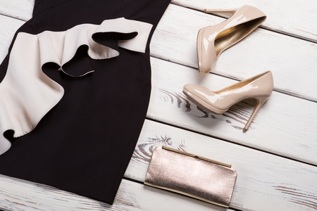 Beige heels and black dress. Beige glossy heels on showcase. Girl's brand new luxury shoes. Stand out from the crowd.