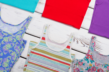 Lots of colorful t-shirts on wooden background. Summer clothing collection. Stock Photo