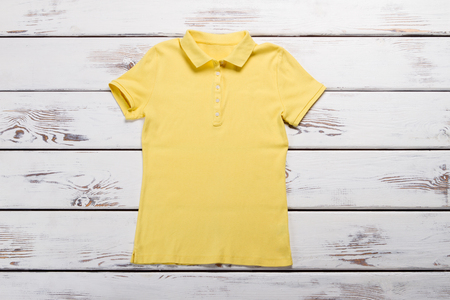 New yellow polo shirt. Womens T-shirt on a wooden background.