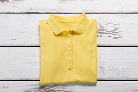 Beautifully folded polo shirt. Yellow T-shirt on showcase of store. Stock fotó