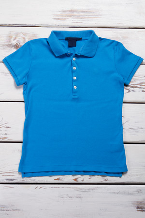Beautiful blue womens T-shirt. Polo shirt on a wooden display case. Stock fotó