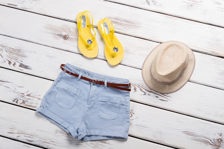 Belted shorts, hat and footwear. Blue shorts on white background. Cotton shorts with small belt. Womans stylish apparel for summer.