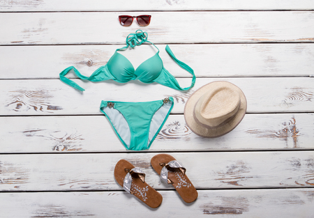 Turquoise swimsuit and aviator sunglasses. Brown flip flops with swimsuit. Womans beachwear on wooden background. Trendy swimwear on sale.