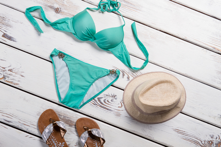 Turquoise swimsuit and flip flops. Single piece swimsuit and hat. Girls beachwear on white shelf. Discounts at local swimwear shop. Imagens
