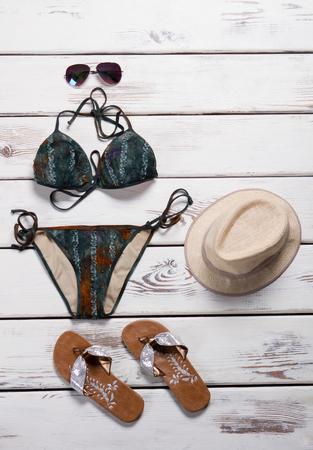 Dark swimsuit with flip flops. Brown flip flops and swimwear. Girls beachwear on store showcase. Seasonal sale of stylish beachwear.
