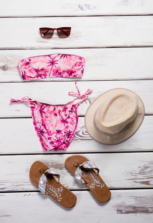 Pink swimsuit with beige hat. Womans pink swimwear and sunglasses. Swimsuit with palm tree pattern. Beachwear made of polyester. Imagens