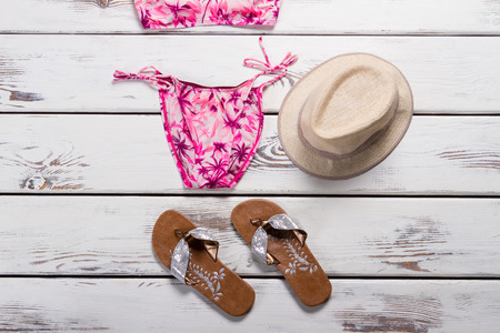 Pink swimsuit, hat and footwear. Woman's beige hat with swimwear. Polyester beachwear with stylish print. Fashionable swimsuit on white table.