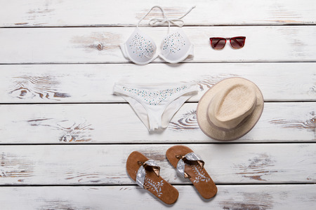 White swimsuit and flip flops. Womans swimwear and dark sunglasses. Brand new beachwear on showcase. Final sale with discounts.