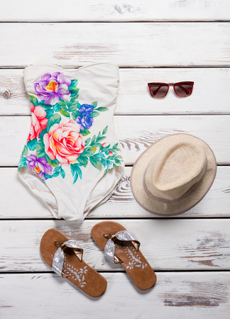 White swimsuit with floral print. Single piece swimsuit and hat. Stylish swimwear on white shelf. Girls quality beachwear with accessories.