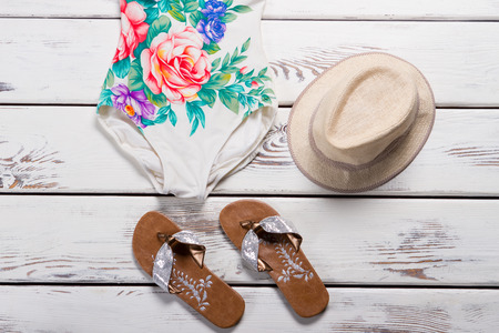 White swimsuit with beige hat. Floral swimsuit and flip flops. Ladys trendy beachwear on table. Quality swimwear and wicker hat.