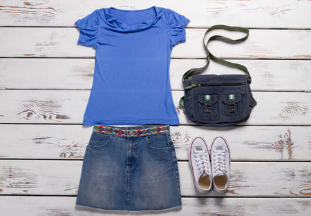 Clothing for teens. Youth womens clothing. Denim skirt with a blue tank top. White sneakers and denim bag. Imagens