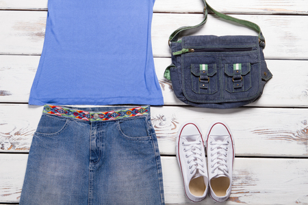 Denim skirt with a blue tank top. Clothing for teens. Youth womens clothing. White sneakers and denim bag.