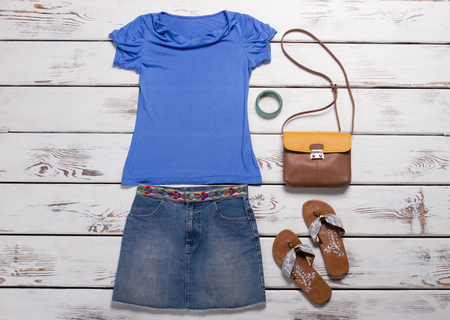 Clothing for teenager. Youth womens clothing. Denim skirt with blue tank top. Summer flip flops and leather handbag.