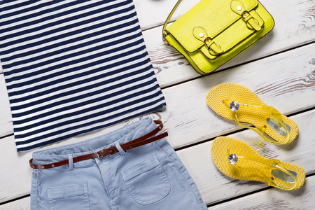 Summer clothes and accessories on a wooden background. Sailor suit, shorts, sandals and handbag.
