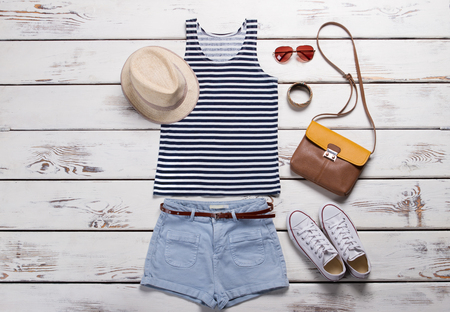 Tank top and blue shorts. Ladys summer outfit on table. Striped tank top with keds. Light shorts with brown belt.