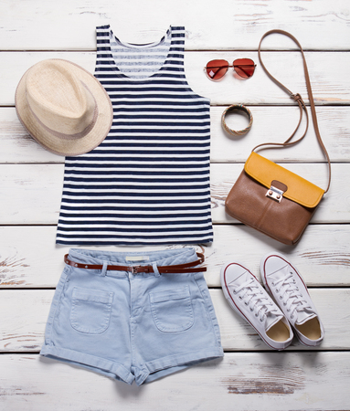 Light shorts with striped top. Girls summer outfit on showcase. Summer clothing and trendy accessories. Female garments with aviator sunglasses. Imagens