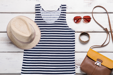 Aviator sunglasses and wicker hat. Womans trendy wear on display. Colorful bracelet with fedora hat. Stylish sunglasses and headwear.