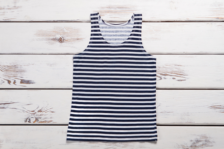 Striped shirt on wooden boards. Mens cothing. Sailor suit for sailor. Imagens