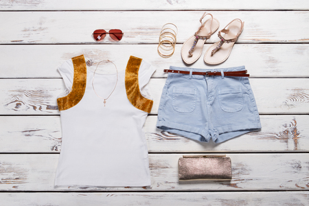 Womens stylish clothing. White t-shirt and denim shorts with accessories. Imagens
