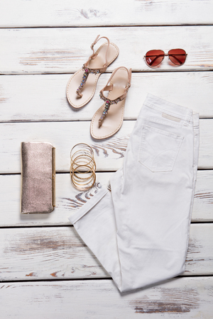 White pants with sandals and accessories on wooden background. Summer clothes set.