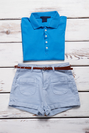 Blue polo shirt and light jeans shorts on a white wooden background.