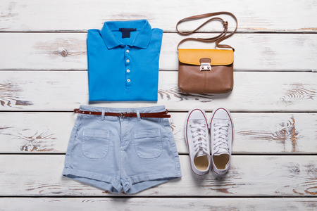 Blue polo shirt and denim shorts. Trendy white gym shoes and handbag on a wooden background. Sports summer outfit.