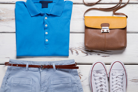 Sports summer outfit. Blue polo shirt and denim shorts. Trendy white gym shoes and bag on a wooden background.