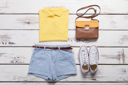 Bright yellow polo shirt and denim shorts. Trendy white gym shoes and a bag on a wooden background. Bright summer outfit.