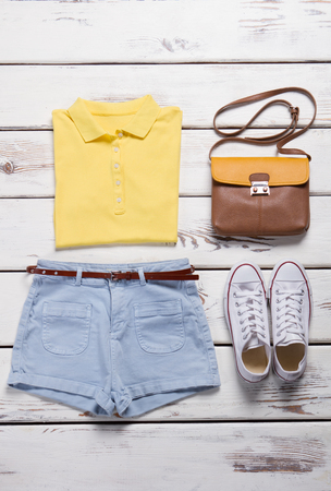 Ladys outfit with jeans shorts. Woodern showcase with female outfit. Casual outfit for teenage girls. Colorful polo and jeans shorts. White sneakers and leather handbag.