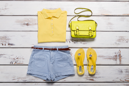 Womans polo shirt and shorts. Female wardrobe on wooden background. Bright female summer outfit. Nice summer outfit with accessories.