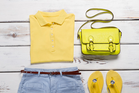 Yellow summer outfit. Yellow polo shirt with denim shorts. Bright sandals and bag. Imagens