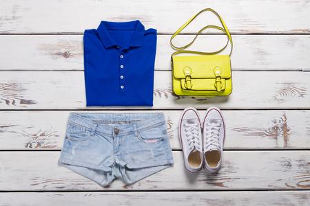 Bright summer sportswear. Denim shorts and a blue polo shirt. White keds and yellow handbag.