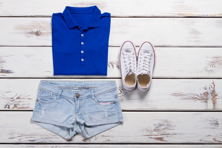 Blue polo shirt and light jeans shorts. White fashion sneakers on a wooden background. Imagens