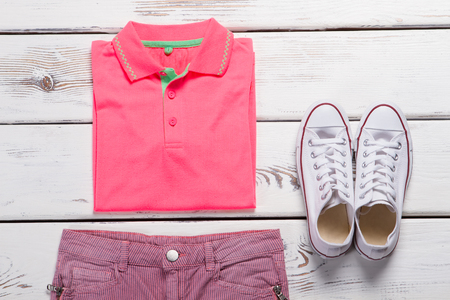 Pink polo shirt, shorts and white sneakers on a wooden background.