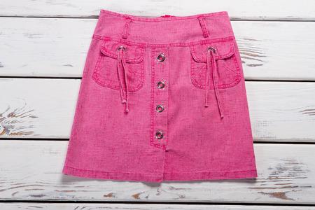 Beautiful pink denim skirt on a wooden background. Imagens