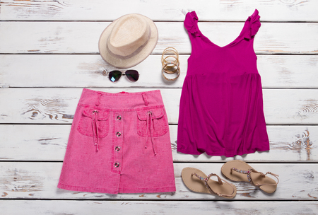 Set of summer clothes. Pink T-shirt and skirt with accessories.