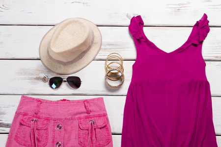 Summer collection of womens clothing. Bright outfit for a young girl. Skirt, shirt, and accessories on the wooden background.