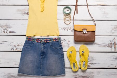 Yellow top and jeans skirt. Denim skirt and flip flops. New clothes on white shelf. Womans casual summer outfit. Zdjęcie Seryjne
