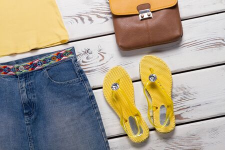 Yellow flip flops and skirt. Brown and orange handbag. Bright-colored footwear for ladies. Seasonal sale in shopping mall. Foto de archivo