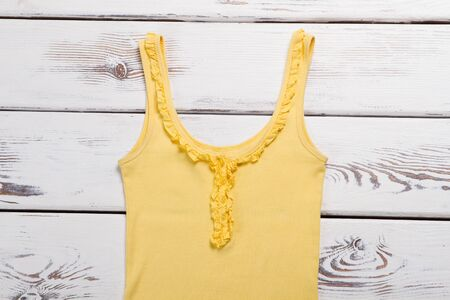 Yellow casual top. Garment on white wooden background. Last size sold at discount. Womans new clothing item.