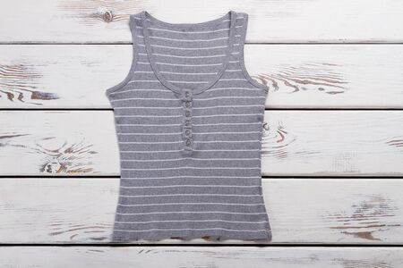 Gray striped tank top. Ladys casual summer top. Garment of high-quality cotton. Clothing item on white table.