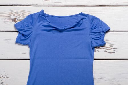 Blue top with crumpled sleeves. Blue t-shirt on wooden background. Casual garment of quality material. Summer top on sale.