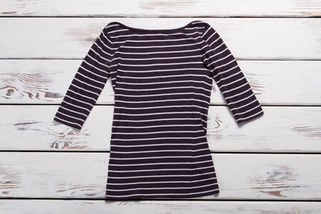 Casual long sleeve top. Striped top on wooden background. Ladys new piece of clothing. Item from spring collection.