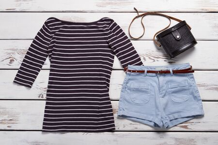 Long sleeve top and shorts. Light blue shorts with belt. Casual clothes and vintage handbag. Girls stylish look for spring. Zdjęcie Seryjne