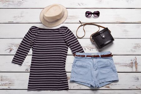 Striped top and beige hat. Dark sunglasses and purse. Womans summer clothing on display. Best prices in shopping mall. Stock Photo
