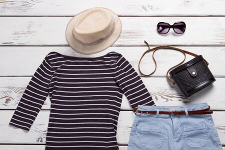 Striped top with beige hat. Black bag and sunglasses. Sale of clothing and accessories. Ladys dark vintage handbag.
