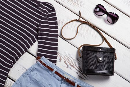 Black purse and sunglasses. Dark bag with a strap. Stylish female accessories. Merchandise on white wooden shelf.