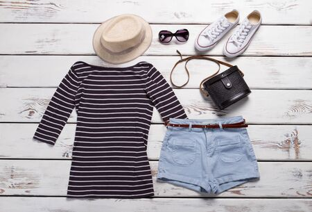 Top with shorts and shoes. Light blue shorts and hat. Girls classic rubber shoes. Clothing sale in shopping mall.